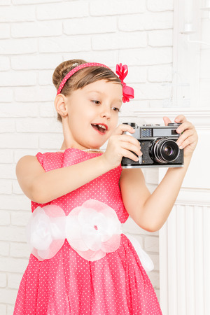 suddenness: little girl looks at retro camera and wonders