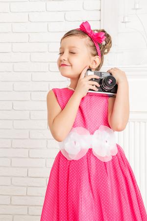 shut: little girl hugging a retro camera eyes shut