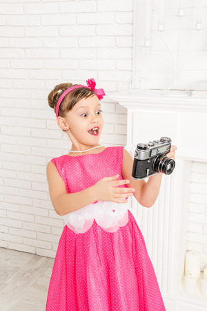 wonders: little girl looks at retro camera and wonders