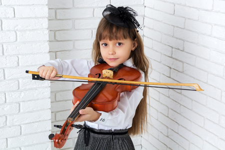 little girl playing the violin, looking at camera
