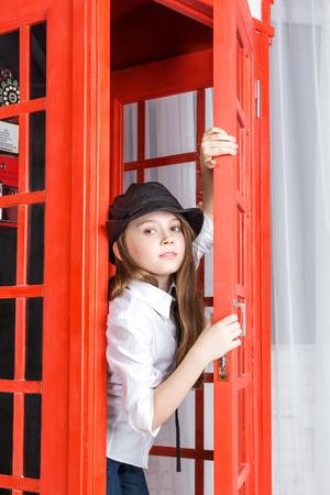 cabina telefonica: ni�a mira hacia fuera de una cabina de tel�fono, primer
