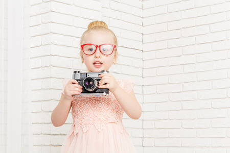 looking away from camera: little girl in glasses with retro camera, looking away