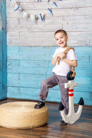 little boy standing and holding an anchor showing tongue Stock Photo