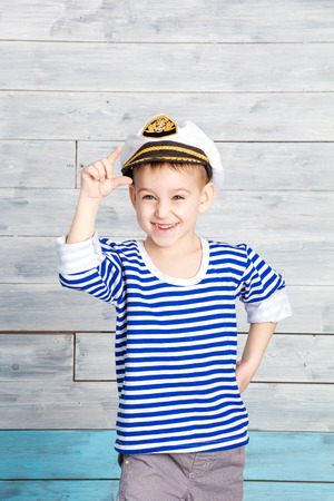 dido: little boy holding on to his cap and laughs, looking at camera