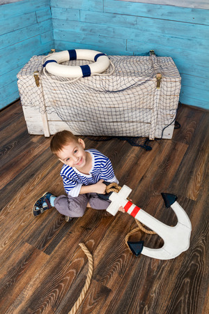 hellion: little boy sitting on the floor and holding the anchor, looking at camera Stock Photo