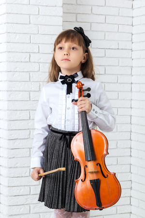 Little girl standing and holding fiddle, looking away