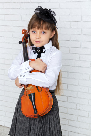 fiddlestick: little girl hugging a violin, looking at camera Stock Photo
