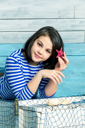 brunets: little girl holds a starfish in hair, looking at camera