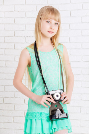 looking away from camera: little girl holding a camera, looking away Stock Photo