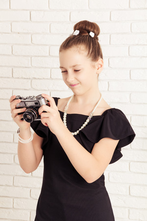 displeased: little girl holding a camera and displeased Stock Photo