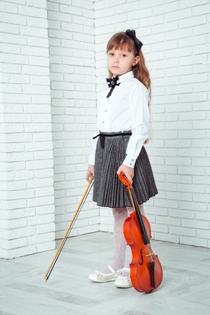 fiddlestick: Little girl standing and holding fiddle, looking at camera