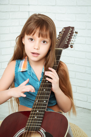 girl studying: little girl playing the guitar and sings, looking at camera