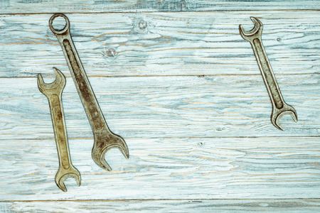 wrenches: flat lay: three wrenches on old boards