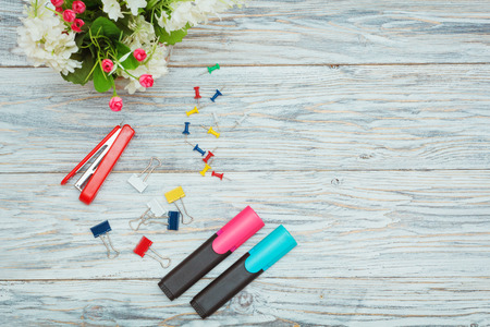 staplers: stationery and flowers on old boards, flat lay Stock Photo