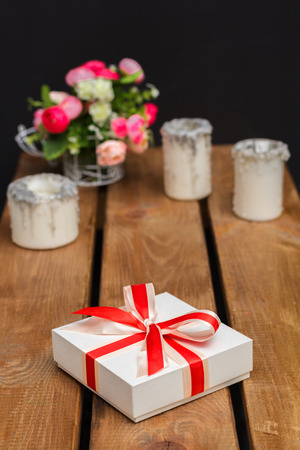 pledge: small birthday gift and flowers in the background Stock Photo