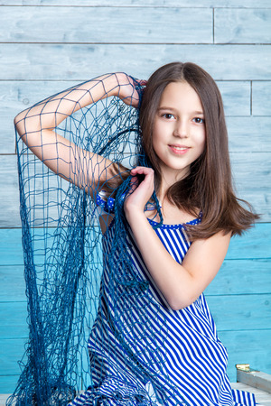 preadolescent: young girl in striped dress with marine network is looking at the camera