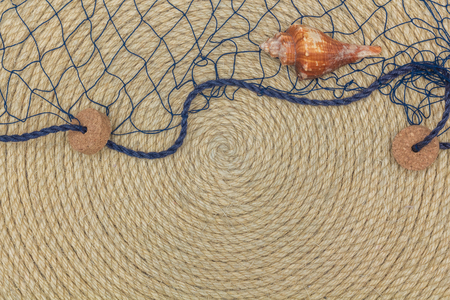 lashing: seashell and marine network lie on background made of rope, flat lay