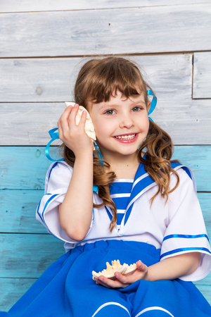 brunets: little girl holding a seashell and laughs, looking at camera Stock Photo