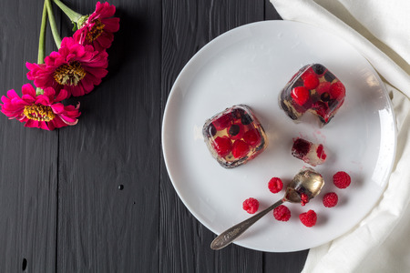 pellucid: Berry jelly on plate and flowers top view. Copyspace