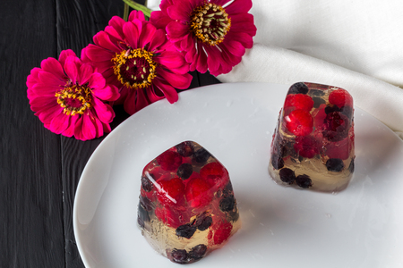 limpid: Berry jelly on plate and flowers. Closeup Stock Photo