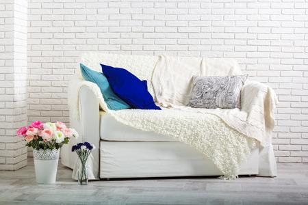 white sofa: white sofa against a white brick wall