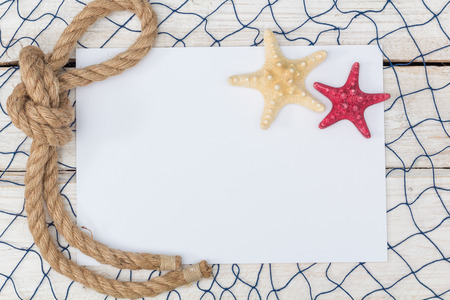 lashing: white sheet of paper, starfish and rope on the old board, flat lay Stock Photo