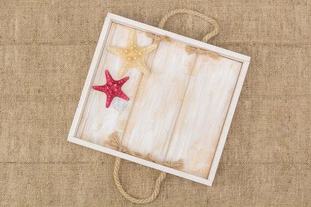 lashing: starfish and a wooden box lying on sacking, flat lay