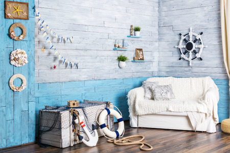 interior in maritime style: sofa, box, helm, anchor and life preserver Stok Fotoğraf - 60577300