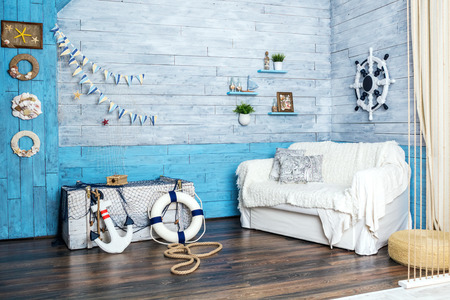 interior in maritime style: sofa, box, helm, anchor and life preserver