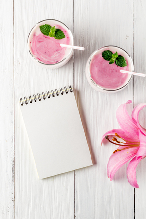 Berry smoothie with yogurt and notepad, flat lay