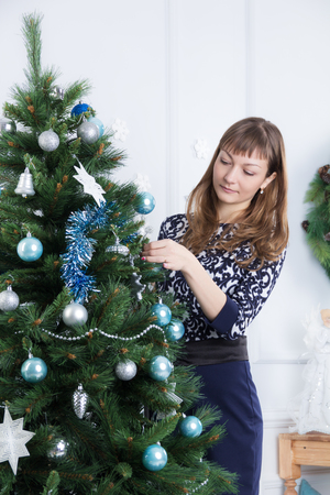decorates: Beautiful young girl decorates the Christmas tree Stock Photo