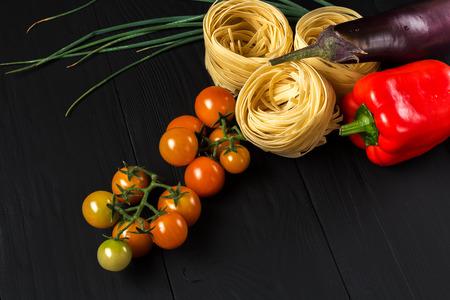 macarrones: pasta y verduras en el fondo negro, primer Foto de archivo