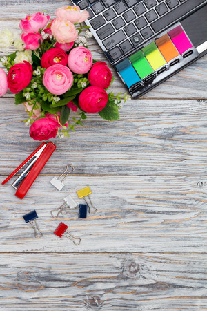 engrapadora: stationery, flowers and laptop on old boards, flat lay