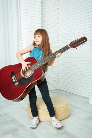 acoustics: little girl stands with a guitar and smiling