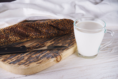 Breakfast: glass of milk and loaf. Closeup