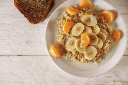 Oatmeal with tangerine and banana for breakfast. Top view