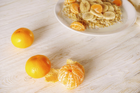 Oatmeal with tangerine and banana for breakfast