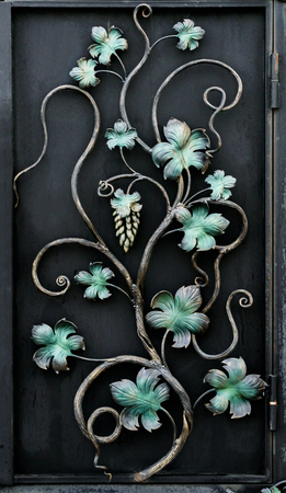 Beautiful forged metal ornament on a black background close-up