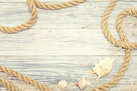 Seashell and rope on a light wooden background Standard-Bild