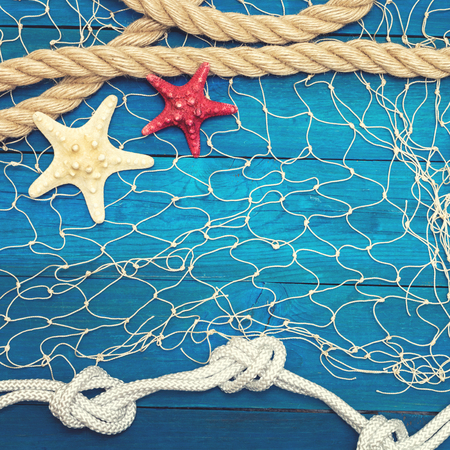 Starfish and seashell on a blue wooden background