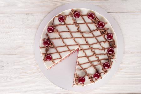 Schokoladenkuchen mit Mousse, dekoriert mit Kirschen und Schokolade. Exemplar Standard-Bild - 98223686