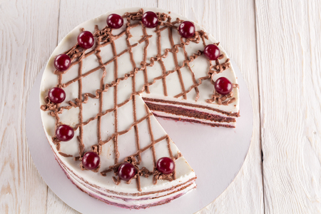 Chocolate cake with mousse, decorated with cherries and chocolate. Closeup