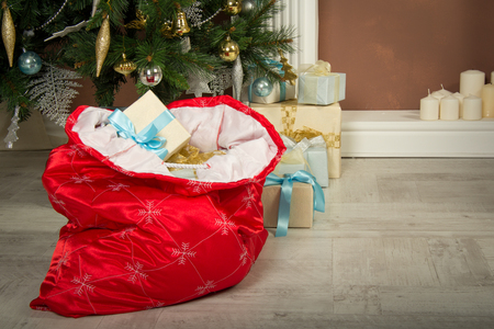 Red sack with gifts under the Christmas tree Archivio Fotografico