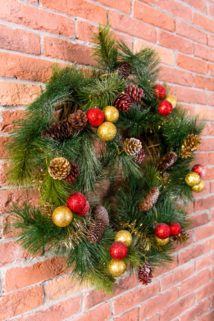 Decorative Christmas wreath with toys on a brick wall Archivio Fotografico
