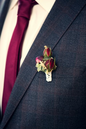 marido y mujer: rose bush boutonniere on grooms grey suit