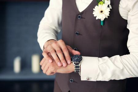 el novio en un chaleco mira el reloj en la habitación Foto de archivo