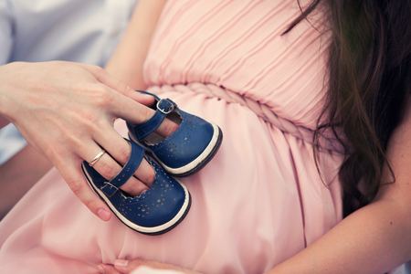 motherhood: baby shoes on the belly of a pregnant woman