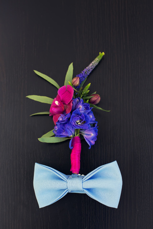 boutonniere: colorful boutonniere and  blue bowtie  on a wooden table