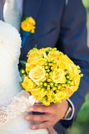 wedding customs: Yellow bridal bouquet of roses in hands Stock Photo