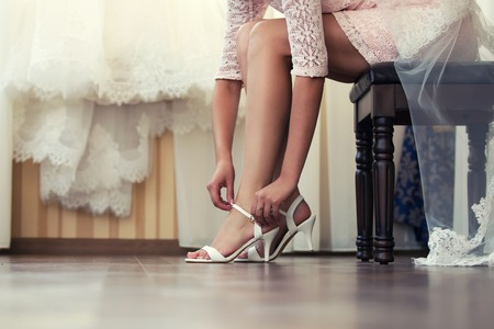 dress shoes: Bride puts his shoes in the morning in the interior Stock Photo